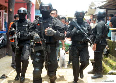Armed anti-terror police walk ahead of guard officers carrying bags of evidence from the house of a man suspected of being involved in Islamic State-related activities in south Tangerang, Indonesia's Banten province, March 22, 2015 in this photo take