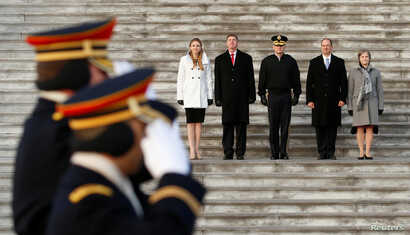 Soldiers salute as they march past stand-ins for President-elect Donald Trump, and his wife Melania (L) and Vice President-elect Mike Pence and his wife Karen (R) during a rehearsal for the inauguration on the East Front of the U.S. Capitol in Washin...
