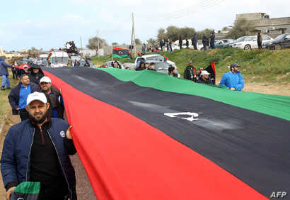 Libyans carry a giant national flag in the capital Tripoli during a celebration to mark the the upcoming eighth anniversary of the Libyan revolution that toppled Moammar Gadhafi, Feb. 25, 2019.