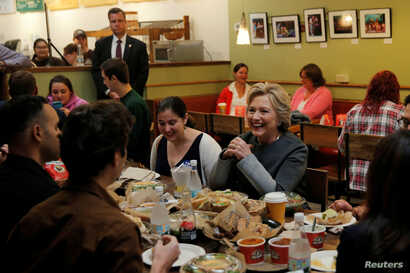 U.S. Democratic presidential nominee Hillary Clinton sits down for lunch with winners of an HFA contest at The Works Bakery Cafe in Durham, New Hampshire, Sept. 28, 2016.