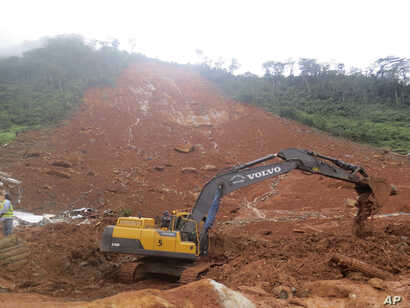 Heavy equipment is used as rescue workers search for survivors and victims following a mudslide in Regent, east of Freetown, Sierra Leone, Aug. 14, 2017.