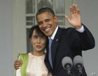 US President Barack Obama, right, waves as he embraces Myanmar democracy activist Aung San Suu Kyi at her residence in Rangoon, Burma, Nov. 19, 2012.