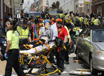 FILE - In this Aug. 12, 2017, photo, rescue personnel help injured people who were hit when a car ran into a large group of protesters after a white nationalist rally in Charlottesville, Va.