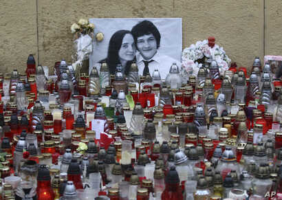 FILE - Candles are seen in front of a photo of journalist Jan Kuciak and his fiancee Martina Kusnirova, in Bratislava, Slovakia, March 9, 2018.