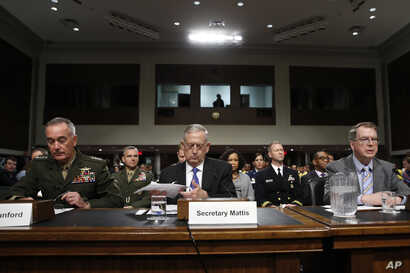 Defense Secretary Jim Mattis, center, flanked by Joint Chiefs Chairman Gen. Joseph Dunford, left, and Defense Undersecretary David Norquist, prepares to testify on Capitol Hill in Washington, June 13, 2017, before a Senate Armed Services Committee he...