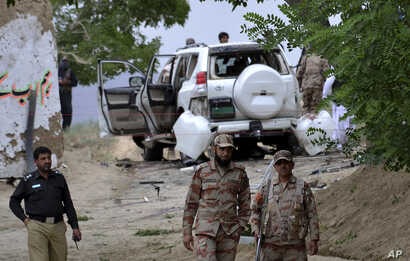 Pakistani security officials stand guard at the site of a suicide bombing which killed dozens of people and left many injured in Mastung district near Quetta, Pakistan, May 12, 2017.