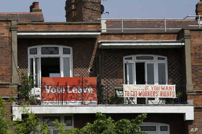 FILE - Banners of opposing views on Britain's so-called Brexit referendum on EU membership are displayed on the balconies of two neighboring apartments in the Gospel Oak area of north London, May 27, 2016. British voters will decide on June 23 on whe...