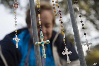 Lupe Cantu, of McAllen Valley, Texas, hangs rosary beads on a barricade along Benjamin Franklin Parkway as she waits for Mass delivered by Pope Francis in Philadelphia, Sept. 27, 2015.