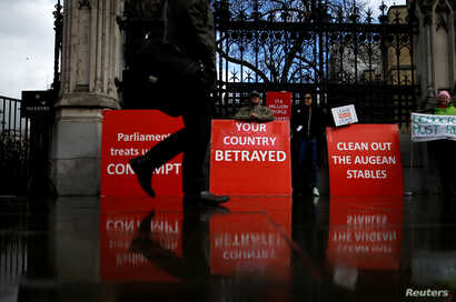 FILE - A person walks past pro-Brexit protesters outside the Houses of Parliament, April 4, 2019.