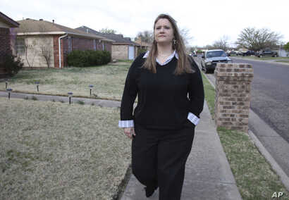 Kristie King walks through her Amarillo, Texas, neighborhood, March 24, 2017, about a week after she had been terminated from her security contractor job in Iraq.