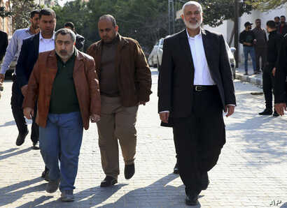 Hamas' supreme leader, Ismail Haniyeh, center right, tours destroyed buildings, in Gaza City, March 27, 2019. Haniyeh made his first public appearance since a new round of cross-border violence with Israel this week.
