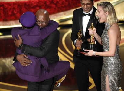 "Samuel L. Jackson, center left, embraces Spike Lee, winner of the award for best adapted screenplay for ""BlacKkKlansman"" as Brie Larson, right, looks on, at the Oscars on Feb. 24, 2019, at the Dolby Theatre in Los Angeles."