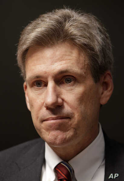 In this Monday, April 11, 2011 file photo, U.S. envoy Chris Stevens stands in the lobby of the Tibesty Hotel where an African Union delegation was meeting with opposition leaders in Benghazi, Libya.