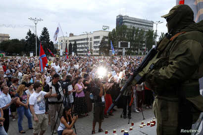 A pro-Russian separatist stands guard during a rally in support of Novorossiya on Lenin Square in the center of the eastern Ukrainian city of Donetsk, July 13, 2014.