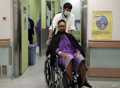 Ken Tsang, a member of a local pro-democracy political party, is admitted at a hospital for a medical exam after sustaining injuries during a clash between protesters and police in an occupied area near government headquarters in Hong Kong, Oct. 15, ...