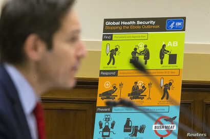 U.S. Centers for Disease Control and Prevention (CDC) Director Tom Frieden displays CDC educational materials as he testifies about the Ebola crisis in West Africa during a hearing of a House Foreign Affairs subcommittee on Capitol Hill in Washington...