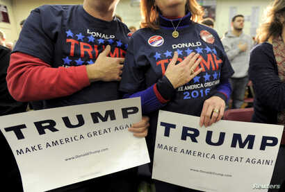 Supporters of U.S. Republican presidential candidate Donald Trump hold their hands to their chest as the national anthem is played at a campaign rally in Concord, New Hampshire, Jan. 18, 2016.