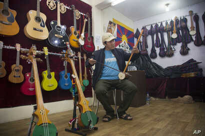 Passang Topgyal, a 38-year-old exile Tibetan, tests a Tibetan stringed musical instrument called a piwang at his instrument shop in Dharmsala, India, June 20, 2017.