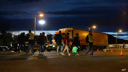 Refugees make their way through a street at the border between Austria and Germany, in Freilassing, southern Germany, Friday, Sept. 18, 2015.