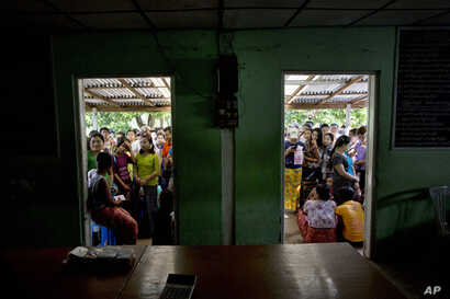 FILE - In this Sept. 29, 2015 photo, hopeful employees stand outside a government labor office to get a labor-card, which enables them to apply for work in the Hlaing Tharyar industrial zone on the outskirts of Yangon, Myanmar.