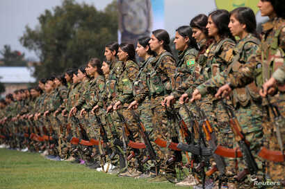 Kurdish female fighters of the Women's Protection Unit (YPJ) take part in a military parade as they celebrate victory over the Islamic state, in Qamishli, Syria, March 28, 2019.