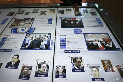 A visitor, top, looks at an electronic screen displaying images and convicted corruption charges of China's fallen politicians, Bo Xilai, bottom second right, Zhou Yongkang, bottom left, and other senior officials, at the China Court Museum in Beijin...