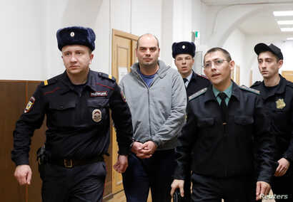 Former Chairman of Vostochny Bank board Alexei Kordichev, who was detained on suspicion of embezzlement, is escorted inside a court building in Moscow, Russia, Feb. 15, 2019.
