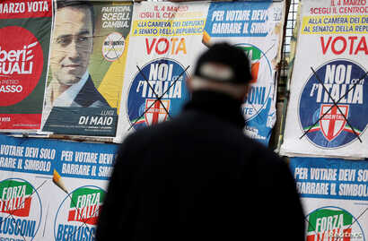 A man stands in front of campaign posters in Pomigliano D'Arco, near Naples, Italy, Feb. 21, 2018.