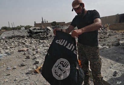 A fighter of the Christian Syriac militia burns an IS flag on the front line on the western side of Raqqa, northeast Syria, July 17, 2017.