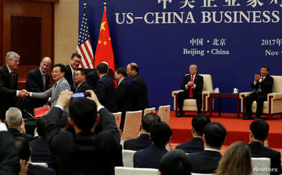 China's President Xi Jinping and U.S. President Donald Trump witness U.S. and Chinese business leaders signing trade deals at the Great Hall of the People in Beijing, China, Nov. 9, 2017.