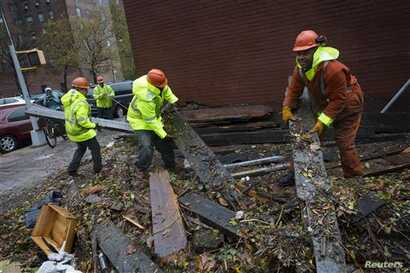 Workers clear debris outside Consolidated Edison power sub-station on 14th Street, New York, Oct. 30, 2012.