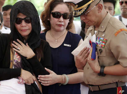 Philippine Marine Brig.Gen. Alvin Parreno (right) prepares to hand the folded national flag to Leslie Abad (left) the widow of First LT. Raymond Abad of the Philippine marines, June 20, 2017, at the Heroes Cemetery in Taguig city, east of Manila, Phi...