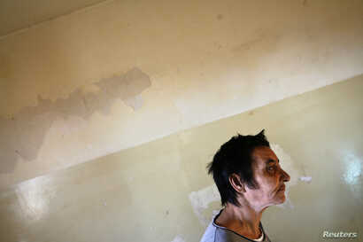FILE - A patient is seen walking toward a group therapy room at a mental health institution in the Balkans.