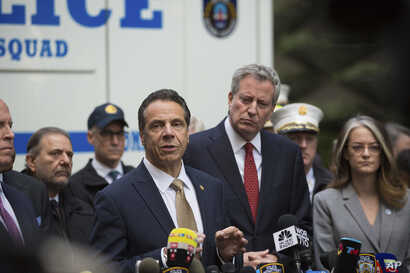 Mayor Bill de Blasio looks on as Gov. Andrew Cuomo delivers remarks during a news conference after NYPD personnel removed an explosive device from Time Warner Center, Oct. 24, 2018, in New York.