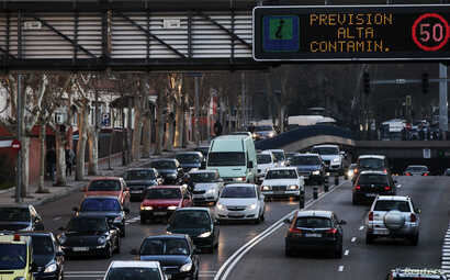 """A sign warns drivers of """"High levels of pollution expected"""" in Madrid, Feb. 8, 2011."""