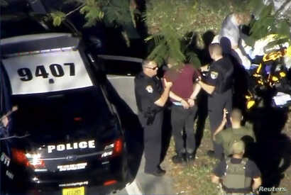 A man placed in handcuffs is led by police near Marjory Stoneman Douglas High School following a shooting incident in Parkland, Florida, Feb. 14, 2018 in a still image from video.