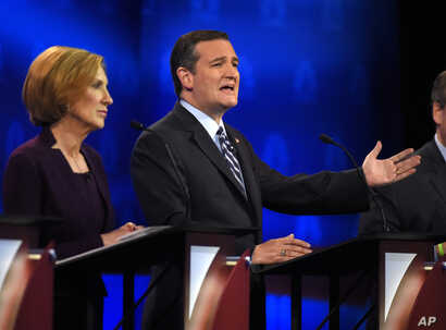 Ted Cruz, right, makes a point as Carly Fiorina looks on during the CNBC Republican presidential debate at the University of Colorado, in Boulder, Colo., Oct. 28, 2015.