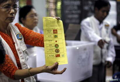 Volunteers count votes at a polling station during Myanmar general elections in central Yangon, Nov. 8, 2015.