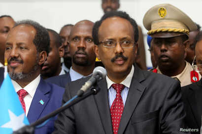 Somalia's newly elected President Mohamed Abdullahi Farmajo flanked by outgoing president Hassan Sheikh Mohamud (L) addresses lawmakers after winning the vote at the airport in Somalia's capital Mogadishu, Feb. 8, 2017.