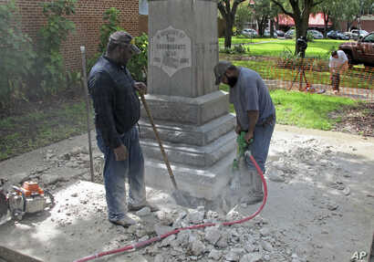 Workers begin removing a Confederate statue in Gainesivlle, Fla., Aug. 14, 2017. The statue is being returned to the local chapter of the United Daughters of the Confederacy, which erected the bronze statue in 1904.