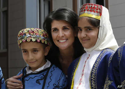 U.S. Ambassador to the U.N. Nikki Haley, center, poses for pictures with Syrian refugee children at the Sakirpasa Umran school, funded by the US government, during its opening ceremony in Adana, southern Turkey, May 24, 2017.