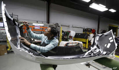 FILE - Final inspector Mary Skinner inspects the rear end of a General Motors Chevrolet Cruze at Jamestown Industries, Nov. 28, 2018, in Youngstown, Ohio.