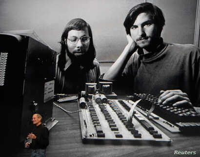 "Apple Chief Executive Officer Steve Jobs stands beneath a photograph of him and Apple-co founder Steve Wozniak from the early days of Apple during the launch of Apple's new ""iPad"" tablet computing device in San Francisco, California, January 27, 2010"