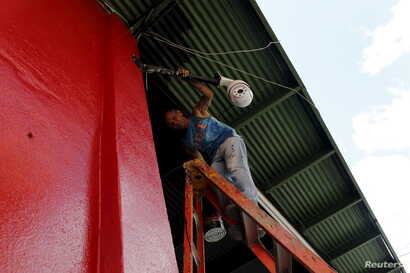 """Cuban migrant Barbaro Rodriguez, 43, who ran out of money, works painting a private business in Paso Canoas, Panama, March 22, 2016. """"I am presently earning $20 a day painting this building. Hopefully, I can make enough money to continue our journey""""..."""