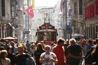 FILE - People walk in central Istanbul's Istiklal Avenue, the main shopping road of Istanbul, in this photo dated Wednesday, Aug. 22, 2018.  Tourists have returned in droves to Turkey, helped this summer by the sharp fall in the value of the Turkish ...