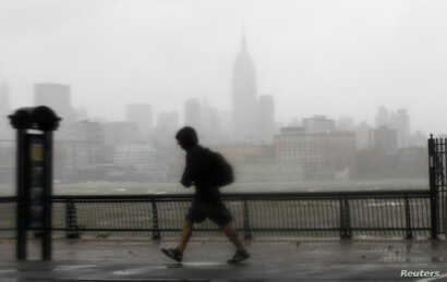 A man walks into the wind across the Hudson River from the skyline of New York in Hoboken, New Jersey, October 29, 2012.