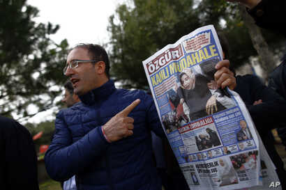 """A man shows the front page of the daily Ozgur with a headline that reads """" bloody intervention """" as people gather outside the headquarters of Zaman newspaper in Istanbul, March 6, 2016."""