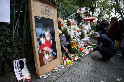 A woman lights candles to pay respect in front of the Bataclan concert hall in Paris, Nov. 13, 2016.