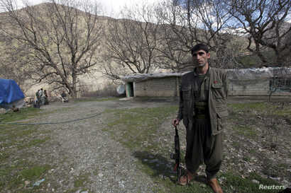 FILE - A Kurdistan Workers' Party (PKK) fighter stands guard at the Qandil mountains near the Iraq-Turkish border in Sulaimaniya, 330 km (205 miles) northeast of Baghdad, March 24, 2013.
