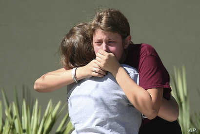 Students grieve outside Pines Trail Center where counselors are present, after Wednesday's mass shooting at Marjory Stoneman Douglas High School in Parkland, Florida, Feb. 15, 2018.